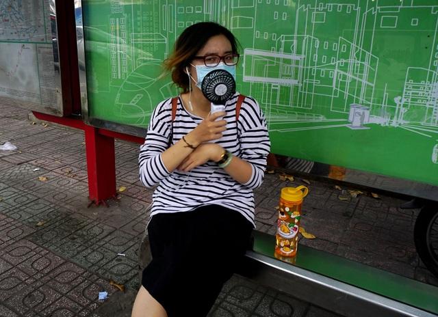 Một cô gái dùng quạt di động làm mát khi ngồi đợi xe bus ở đường Phạm Ngọc Thạch, quận 1.