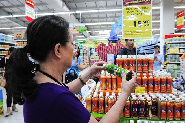 Một vị khách lớn tuổi đang xem các thông tin trên vỏ chai tại khu vực bán sản phẩm TH true Herbal trong siêu thị Big
