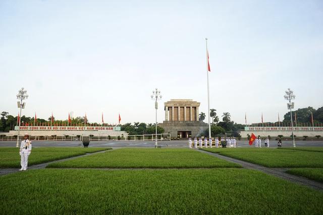 Nhạc Quốc ca vang lên, mọi hoạt động trên quảng trường tạm dừng, người dân hướng về cột cờ phía trước lăng Chủ tịch Hồ Chí Minh.