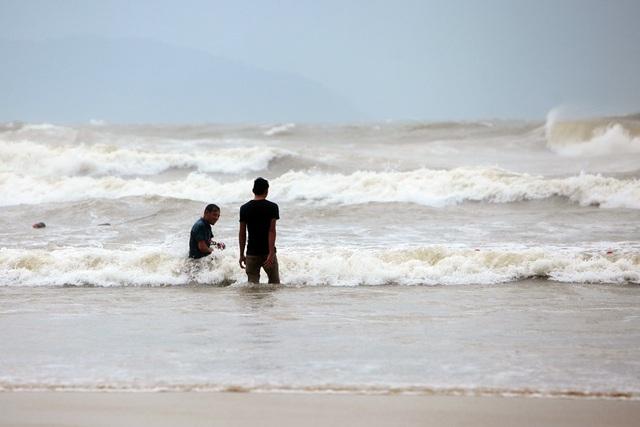 Hai ngư dân thu lưới trước sóng mạnh trên bờ biển Mỹ Khê.