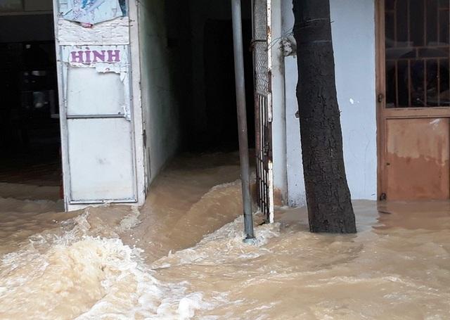Nước từ khu vực đồng ruộng phía sau chảy cuồn cuộn qua nhà dân