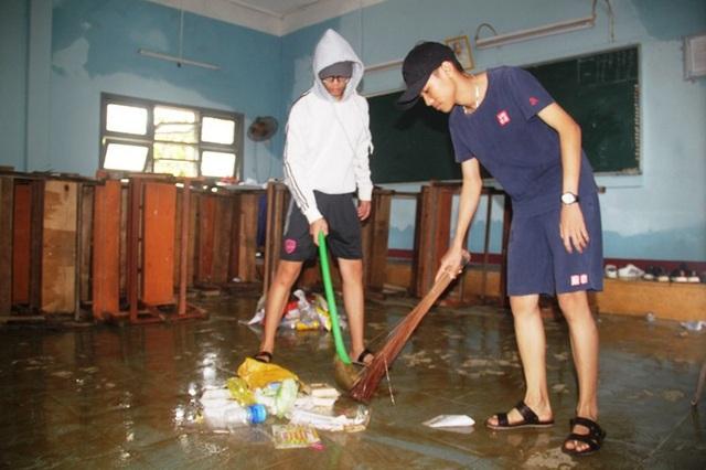 Nước rút dần, các em học sinh Trường THPT số 1 Tuy Phước 1 (huyện Tuy Phước) đến trường dọn bùn để chuẩn bị đi học lại.