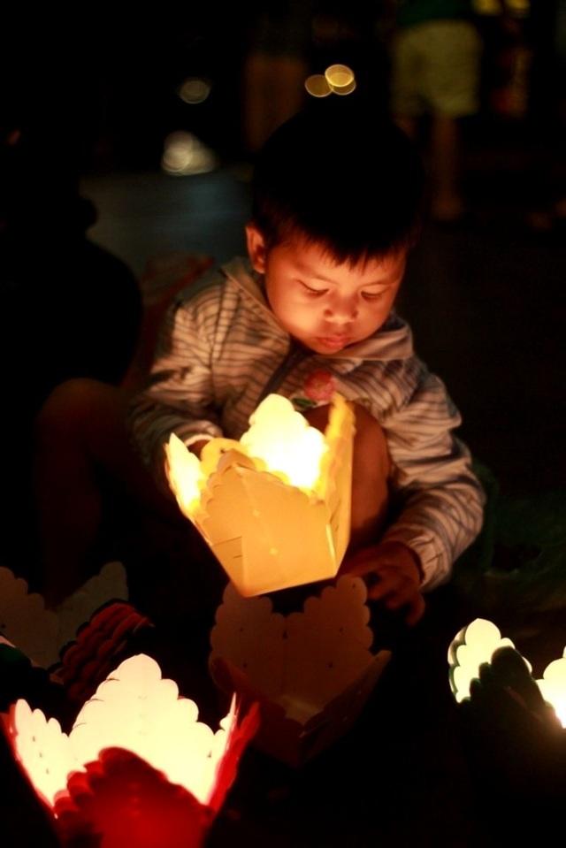 """Cậu bé Bi cùng mẹ bán hoa đăng cho khách trong đêm giao thừa 31/12 cười vui vẻ: """"Con mong năm mới con sẽ cao thêm, có nhiều đồ chơi hơn nữa. Và mẹ con bán được thật nhiều hoa đăng có thêm tiền mua bánh, đồ ăn ngon cho con nữa"""""""