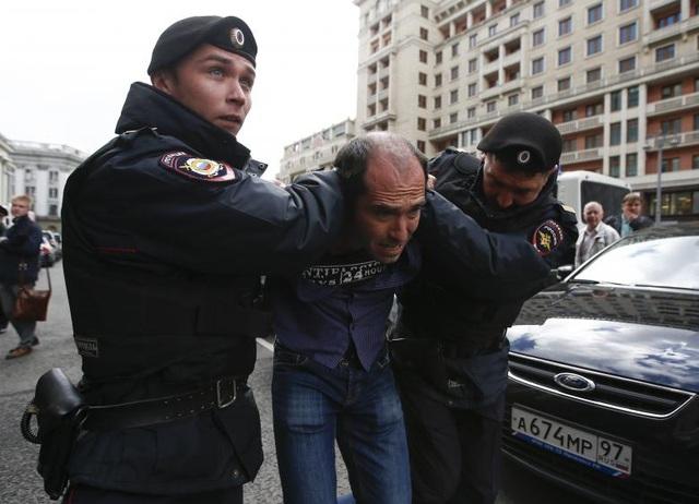 Một người đàn ông bị bắt khi biểu tình bên ngoài Hạ viện Nga (Ảnh: Reuters)