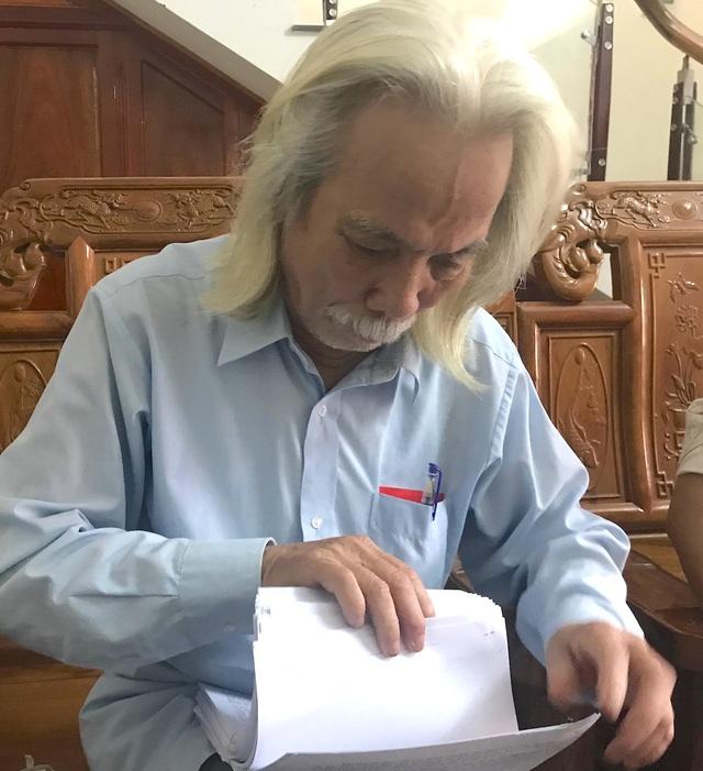 Ông Nam lật giở từng trang hồ sơ đi kiện cho PV xem.