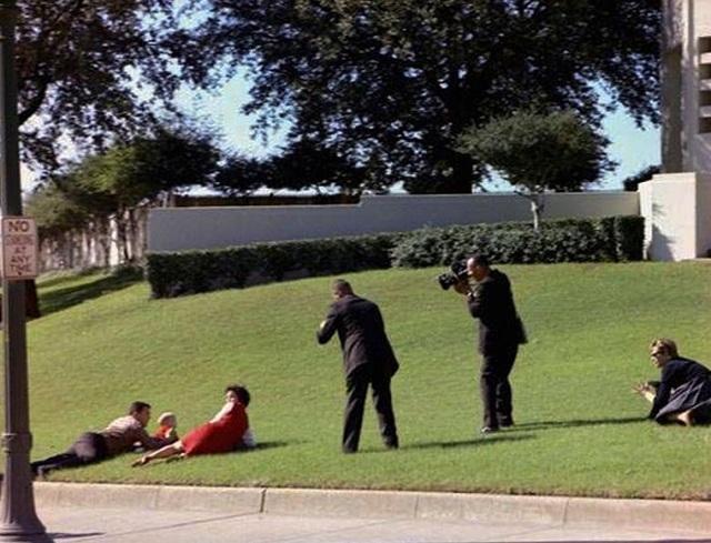 Bill và Gayle Newman, 2 nhân chứng vụ ám sát ôm lấy con mình khi tiếng súng nổ ra. Trong khi đó, các phóng viên của CBS News vẫn hăng hái chụp ảnh