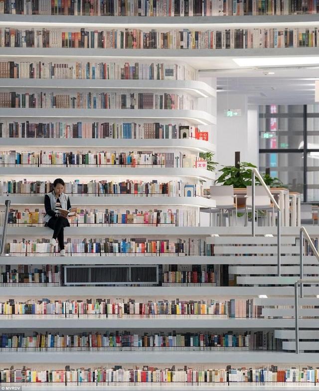 """Thư viện mở ra trên diện tích khổng lồ 34.000m2, với các giá sách được xây chìm vào trong tường, đối với các giá sách """"lộ thiên"""" - chúng sẽ được thiết kế để đồng thời tạo thành những bậc thang, những chỗ ngồi cho người đọc."""