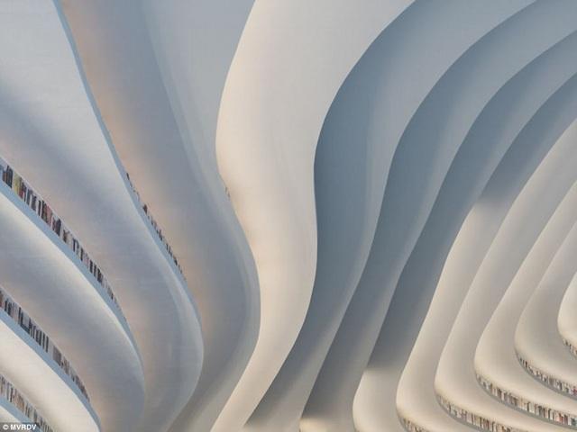 Những giá sách uốn lượn tạo nên nét duyên dáng cho kiến trúc, tạo nên sự đa tầng của nội thất, đi cùng với đó là các hiệu ứng ánh sáng.