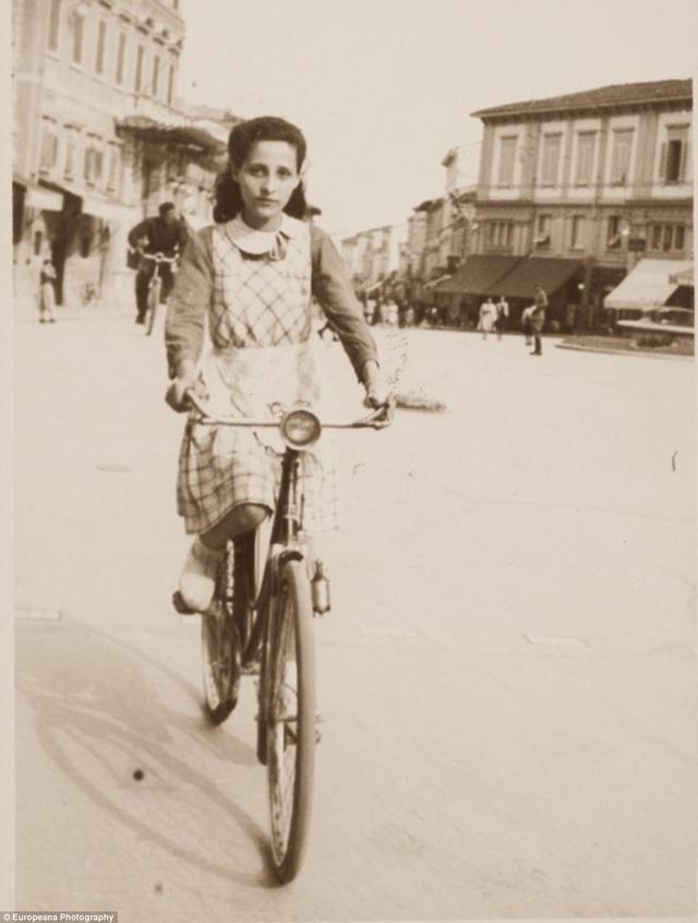 Một phụ nữ trẻ người Ý đang đạp xe trong thị trấn ở vùng Tuscany.