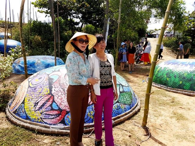 Du khách chụp ảnh lưu niệm với làng nghệ thuật thuyền thúng