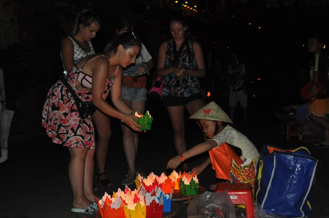 Dọc bờ sông Hoài, nhiều người già và cả trẻ em bán đèn hoa đăng cho khách có nhu cầu