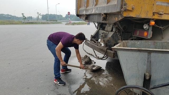 Tài xế phải vất vả thu dọn vật liệu rơi vãi xuống đường.