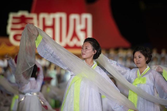 Một nhóm đồng diễn khác với những dải lụa trắng. (Ảnh: AFP)