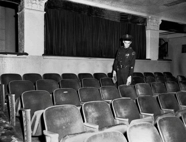 Một cảnh sát chỉ vào chiếc ghế mà tên Oswald đã ngồi lúc hắn bị bắt