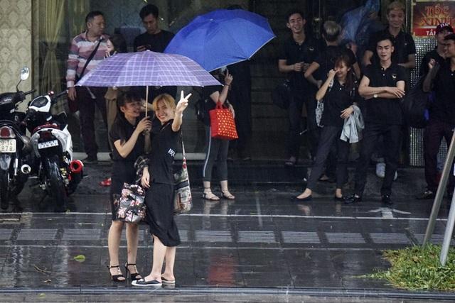 Những người trẻ tỏ ra vui sướng khi thấy cơn mưa quý như vàng trên phố Bà Triệu.
