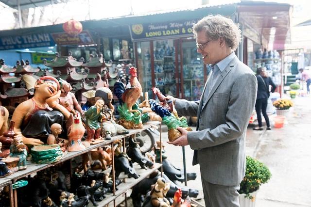 Nhà ngoại giao Thụy Điển ngắm nghía các tượng gà, sản phẩm phổ biến vào dịp cuối năm tại chợ gốm Bát Tràng trước thềm năm mới Đinh Dậu.