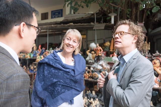 Đại sứ Pereric và phu nhân chăm chú lắng nghe một cán bộ Đại sứ quán Thụy Điển giải thích về ý nghĩa của các sản phẩm đồ gốm tại làng nghề Bát Tràng.