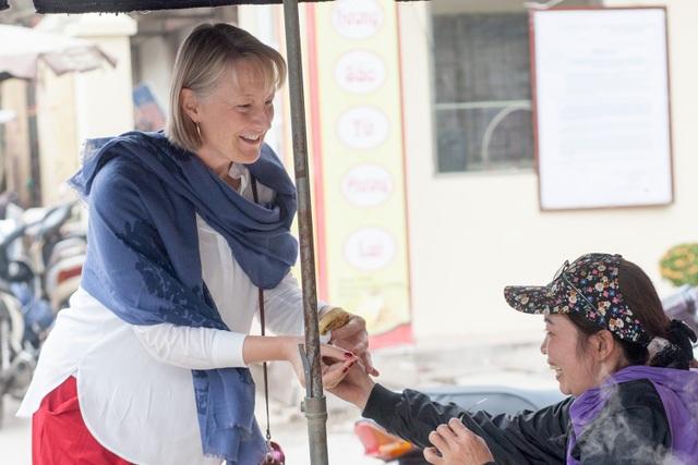 Bà Anna còn thử một sản phẩm bánh của người dân địa phương tại Bát Tràng.