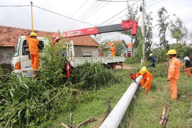 Các công nhân đang tập trung dựng lại cột điện bị ngã đổ