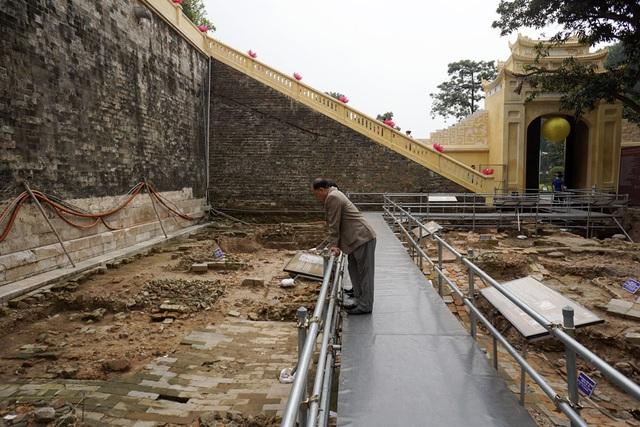 Một khách tham quan đang nhìn xuống dấu tích sân gạch thời Lê Trung Hưng (thế kỷ 17). Mảng sân rộng 5,6m, từ sân Đoan Môn đến đầu hồi kiến trúc hành lang. Đến thế kỷ 18, di tích này đã bị phá hủy để mở rộng kiến trúc hành lang sát với chân cổng Đoan Môn - Hoàng thành Thăng Long.