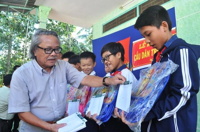 Nhà báo Phan Huy - Trưởng VP đại diện báo Dân trí khu vực ĐBSCL trao học bổng và cặp sách đến các em học sinh