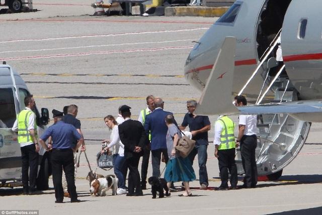 Một nhóm người đứng chờ sẵn trên sân bay để giúp gia đình Clooney di chuyển.