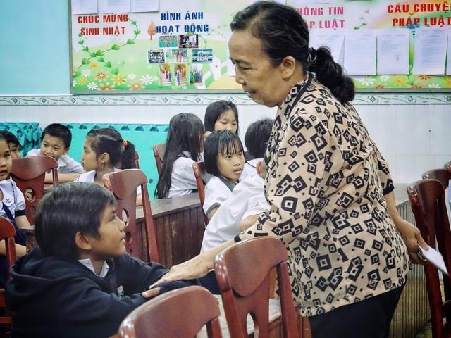 Các cô chú cán bộ làm công tác khuyến học đang thăm hỏi, động viên các em