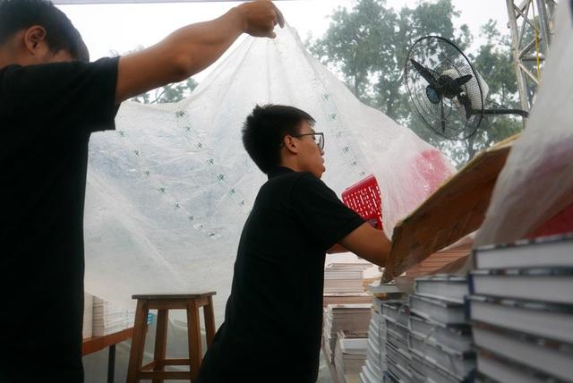 Cơn mưa nặng hạt khiến nhân viên của các gian hàng sách phải nhanh chóng dọn dẹp, che chắn.