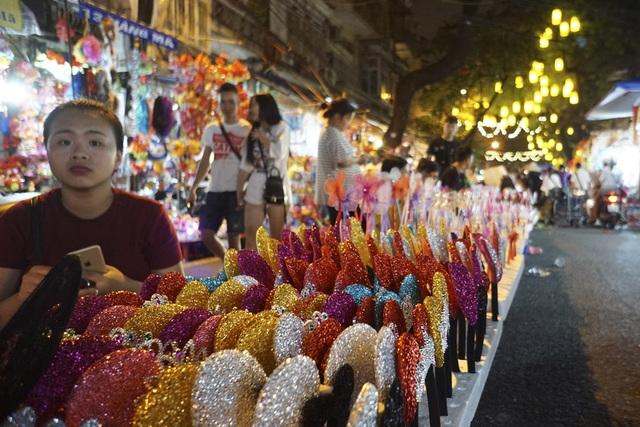 Phố Hàng Mã có thêm một dãy bán hàng giữa lòng đường, chuyên bán các loại bờm tóc, chong chóng, các phụ kiện trang trí cho trẻ nhỏ.
