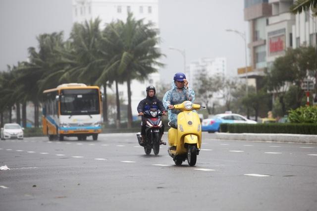 Trên đường Võ Nguyễn Giáp, người đi xe máy phải lấy tay giữ mũ vì gió thổi mạnh.
