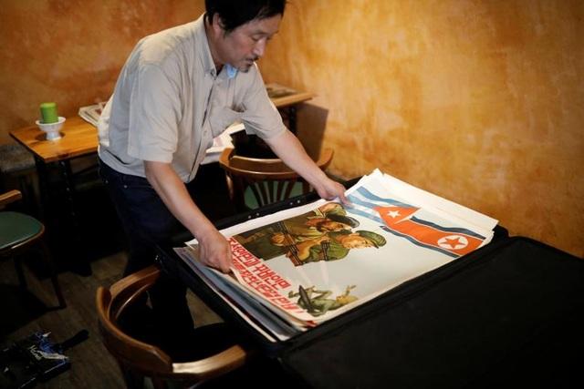 Ông Choi Sang Kyun, chủ phòng trưng bày mang tên Bình Nhưỡng đang sắp xếp những biểu ngữ, tranh tuyên truyền mà ông thu thập được ở Seoul, Hàn Quốc.