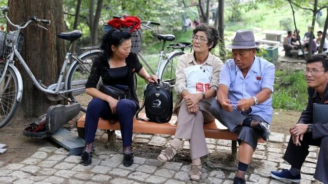 Người phụ nữ ngồi giữa đang sử dụng chiếc túi của thương hiệu bình dân liên doanh Nhật Bản - Trung Quốc Miniso. Theo NK News, Miniso đã mở cửa hàng đầu tiên tại Triều Tiên, tuy nhiên do lệnh trừng phạt, công ty này phải đổi tên thành thương hiệu khác.