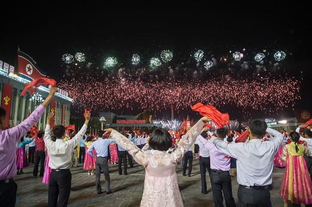 Những người tham gia lễ kỉ niệm cùng vẫy tay khi pháo hoa đang được bắn rợp trời trên tháp Juche. (Ảnh: AFP)