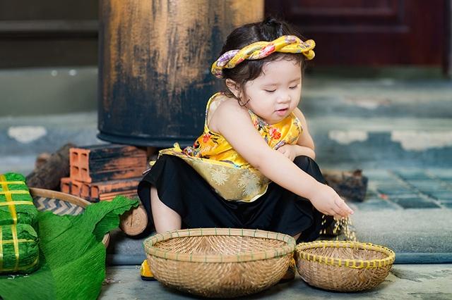 Bé Mimi mặc bộ trang phục bằng gấm cách tân từ trang phục của phụ nữ Việt ngày xưa. Trên đầu cô bé còn đội một chiếc mấn xinh xắn. Đây là kiểu trang phục đang thịnh hành mùa Tết năm nay.