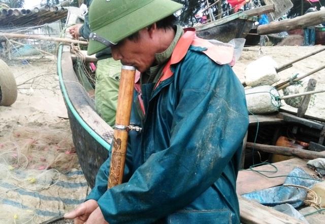 Một ngư dân tranh thủ hút điếu thuốc lào sau chuyến ra khơi lạnh giá