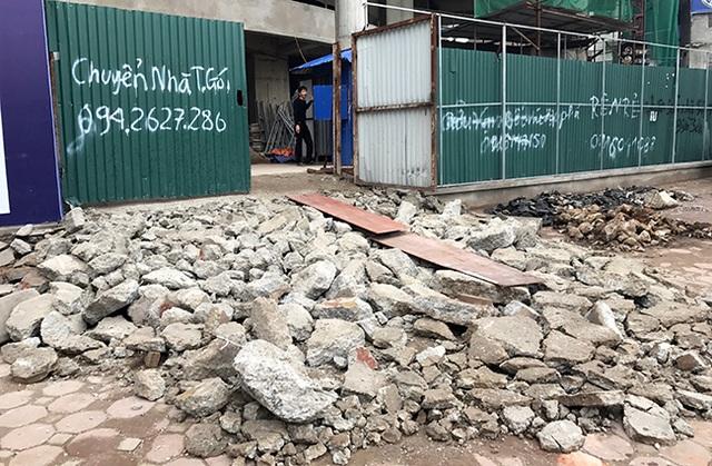 Cả một khối bê tông cốt thép lớn của một tòa nhà cao tầng đang hoàn thiện lấn vỉa hè (đường Tây Sơn) bị máy xúc đào tung