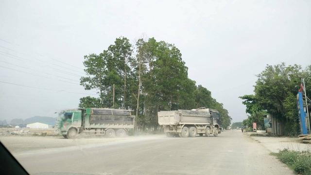 Những chiếc xe tải chở đầy đất đá từ tỉnh lộ 477 vào đổ san lấp khu công nghiệp.