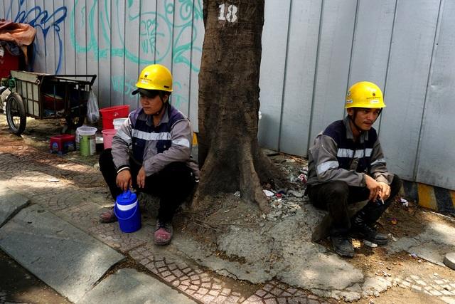 Những công nhân xây dựng nghỉ mệt dưới gốc cây có bóng mát ở quận 1.