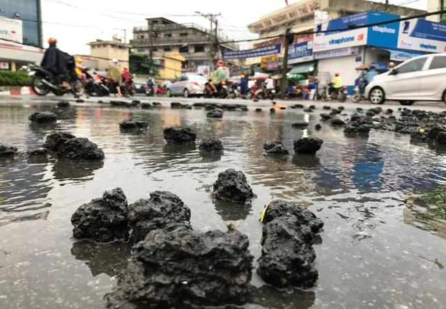 Đất đá, nhựa đường bị nước mưa cuốn trôi nằm la liệt ngay ngã 5 chợ Thủ Đức sau cơn mưa.