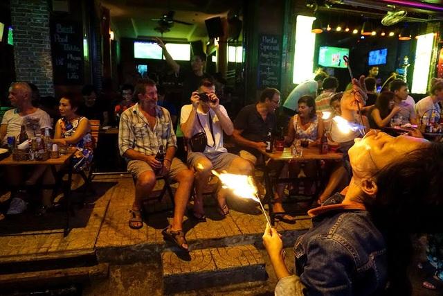 Những người nước ngoài tò mò, dùng máy ảnh ghi lại cảnh chị Sen nuốt lửa.