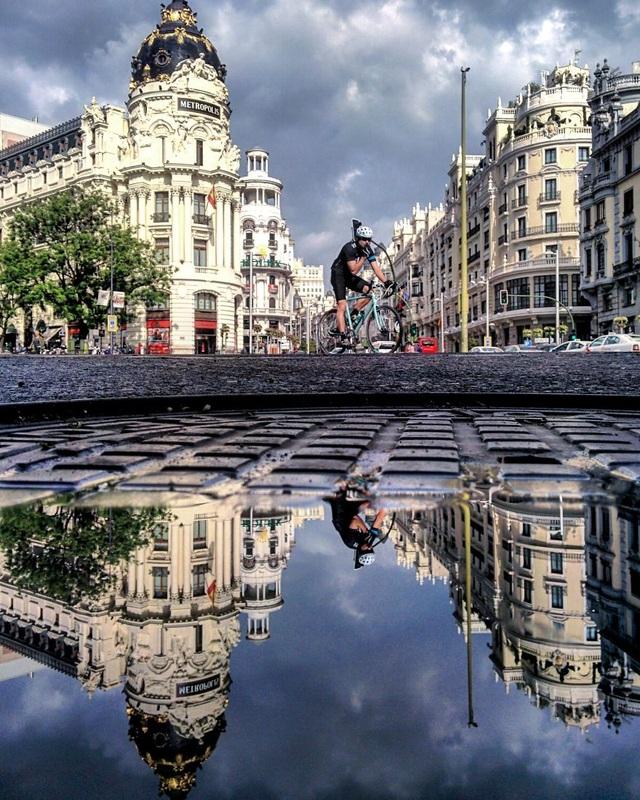 Hình ảnh một người đi xe đạp được tái hiện qua vũng nước.