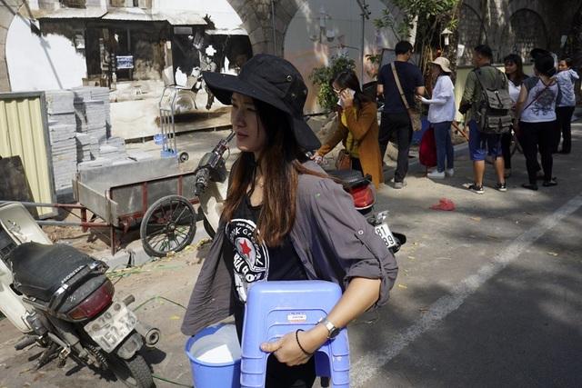 Một nữ họa sĩ Hà Quốc trên đoạn phố Phùng Hưng nơi thực hiện dự án tranh.