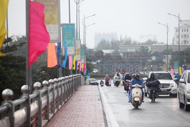 Người dân đi qua cầu sông Hàn dưới trời mưa tầm tã, bên cạnh các pano, băng rôn APEC treo trên các cột đèn.