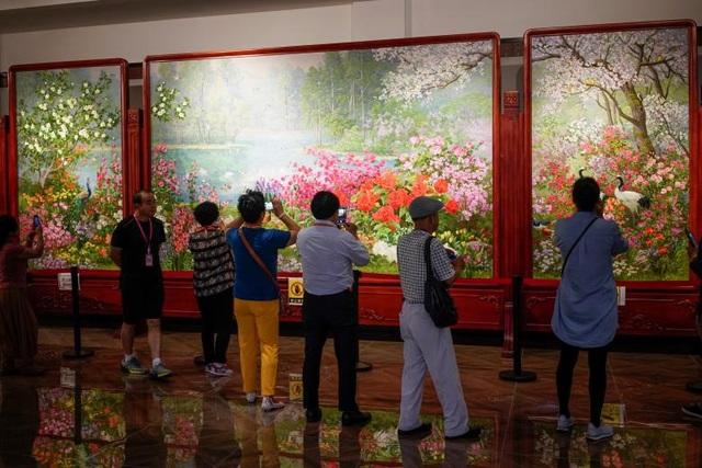Khách tham quan đứng trước những tác phẩm nghệ thuật của các nghệ sĩ Triều Tiên trung tâm văn hóa Trung Quốc - Triều Tiên ở Đan Đông. Nhân viên ở đây cho biết mỗi bức vẽ của nghệ sĩ Triều Tiên được họ bán với giá khoảng 100.000 USD.