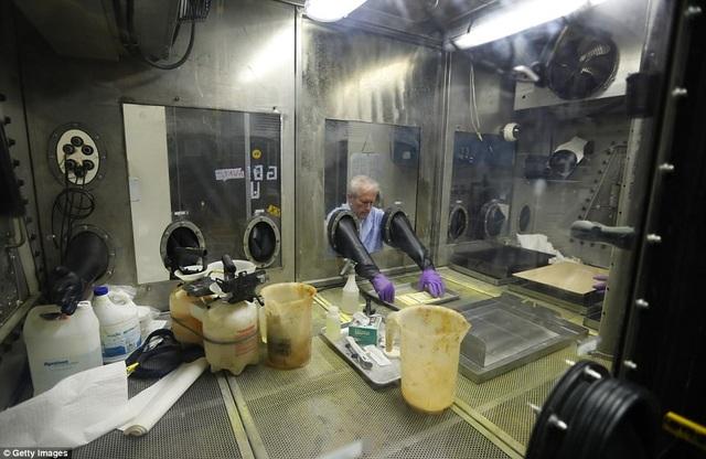 Nhà hóa học Randy Moss thực hiện thử nghiệm thiết bị khử nhiễm mẫu vật nhỏ trong khu vực buồng kín.