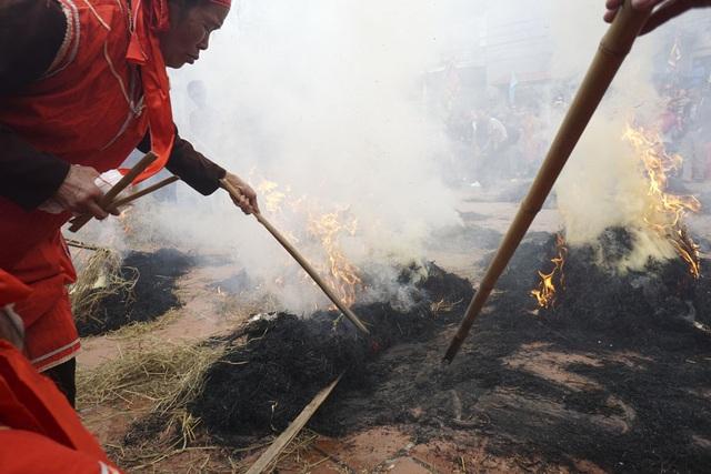 Sau khoảng thời gian thổi trên bếp với ngọn lửa bốc cao, các nồi cơm nhanh chóng được vùi kỹ vào đống rơm đang cháy để ủ cho đến lúc chín.