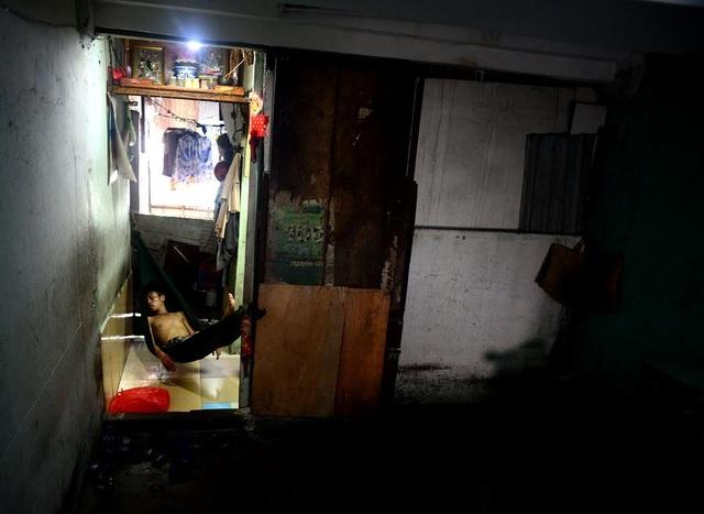 Nhiều gia đình dùng ván gỗ che chắn tạm ở góc cầu thang lên xuống chung cư làm chỗ ở.