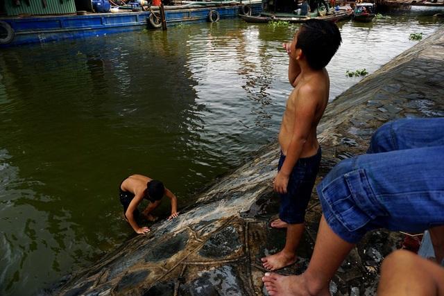Thời tiết TPHCM mấy tuần nay nắng nóng gay gắt, giữa trưa nhiệt độ có thể lên tới 40 độ C khiến cuộc sống của người dân bị đảo lộn. Người Sài Gòn phải tìm đủ mọi cách để chống nóng. Trong ảnh: Những đứa trẻ ngâm mình dưới sông để giảm nhiệt.
