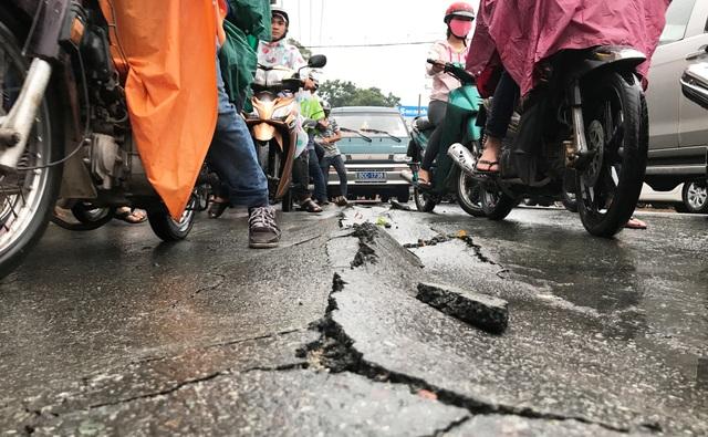 Mặt đường nứt toác, lớp nhựa bị nước cuốn trôi trong cơn mưa cực lớn chiều 18/6 ở quận Thủ Đức, TPHCM.
