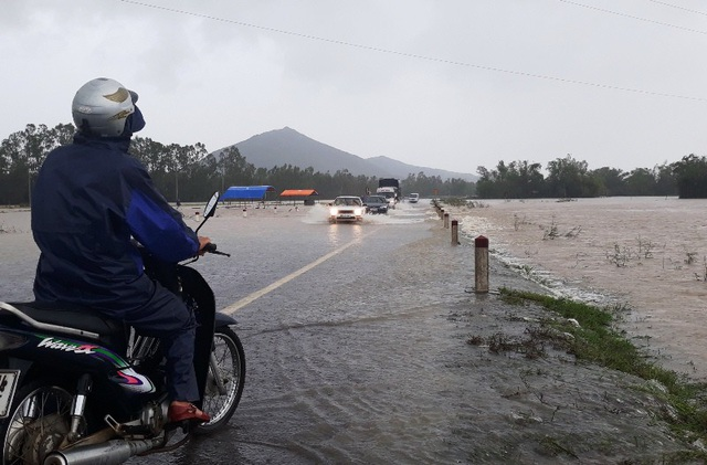 Nước sông dâng cao, nước lũ tràn qua tuyến đường tránh quốc lộ 1 qua thị xã An Nhơn, tỉnh Bình Định